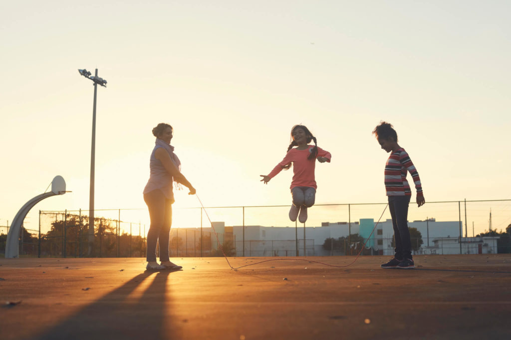 A woman and two children jumping rope