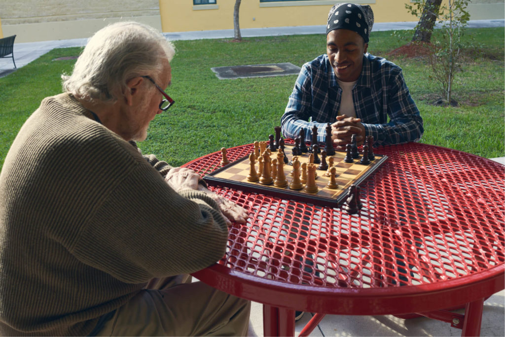 Elderly white man playing chess with a young Black man