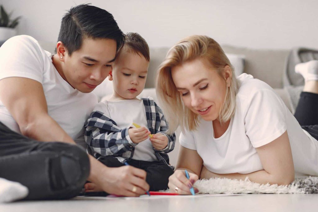 Mother and father coloring with their young son