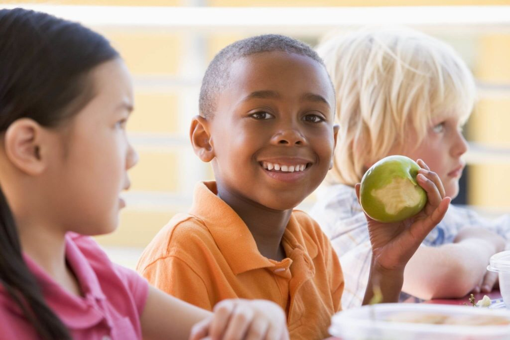 Black boy smiling and holding a green apple