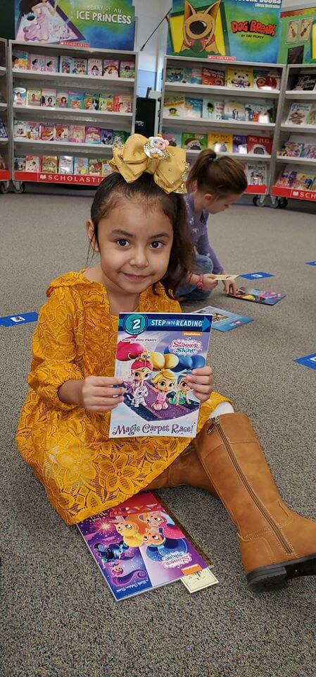 Young girl showing off a book